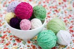 Beaucoup de boules lumineuses du tricotage sur le fond d'une fleur Photo stock