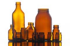 Beaucoup de bouteilles en verre de médecine sur le fond blanc Images libres de droits