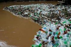 Beaucoup de bouteilles de plastique sur le rivage de la rivière brune Photographie stock libre de droits