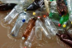 Beaucoup de bouteilles de plastique sur le rivage de la rivière brune Photos stock