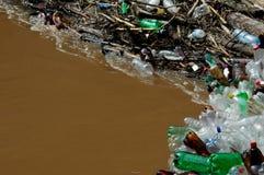 Beaucoup de bouteilles de plastique sur le rivage de la rivière brune Photos libres de droits