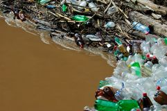 Beaucoup de bouteilles de plastique sur le rivage de la rivière brune Photographie stock