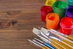 Beaucoup de brosses et de pots de peinture sur le fond en bois de table Image libre de droits