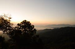 Beaucoup de brume et lever de soleil derrière la montagne Image stock