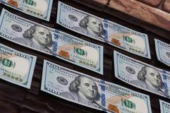 Beaucoup de cent billets d'un dollar sur une table de verre foncé avec la réflexion de briques Photo stock