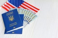 Beaucoup de cent dollars et deux passeports bleus ukrainiens Immigration au concept des Etats-Unis Passeport étranger d'Ukrainien photographie stock libre de droits