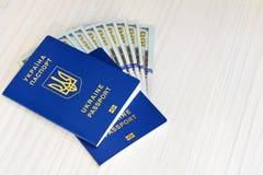 Beaucoup de cent dollars et deux passeports bleus ukrainiens Le concept de la corruption en Ukraine photo stock