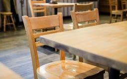 Beaucoup de chaises en bois brunes et table ont placé sur le plancher en bois Photographie stock libre de droits