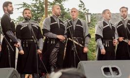 Beaucoup de chanteurs dans des costumes traditionnels géorgiens se tenant sur la scène de la célébration du jour de Mtskheta Image stock
