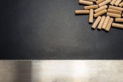 Beaucoup de chevilles et scie en bois de main pour le bois se trouvant à plat sur un fond noir images stock
