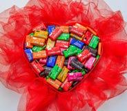 Beaucoup de chocolats avec des messages d'amour dans la boîte en forme de coeur rouge Photographie stock libre de droits