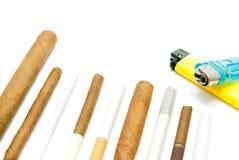 Beaucoup de cigares et d'allumeurs sur le blanc Photographie stock