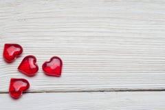 Beaucoup de coeurs en verre rouges sur le fond blanc Images libres de droits