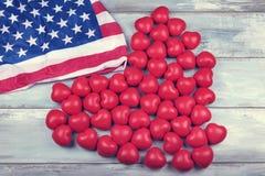 Beaucoup de coeurs et de drapeau américain sur une surface en bois Image libre de droits