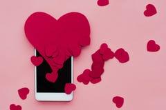Beaucoup de coeurs et smartphone Le concept à aimer dans les réseaux ou l'APP sociaux de dater Fond rose Images libres de droits