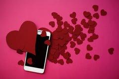Beaucoup de coeurs et smartphone Le concept à aimer dans les réseaux ou l'APP sociaux de dater Fond rose Photos libres de droits