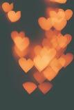 Beaucoup de coeurs oranges sur un fond foncé Photo libre de droits