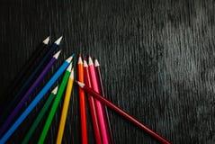 Beaucoup de crayons colorés sur un fond noir Crayons neufs Photographie stock libre de droits