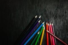 Beaucoup de crayons colorés sur un fond noir Crayons neufs Image libre de droits