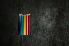 Beaucoup de crayons colorés sur un fond noir Crayons neufs Photographie stock