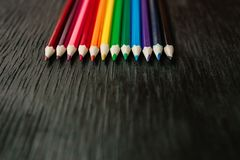 Beaucoup de crayons colorés sur un fond noir Crayons neufs Image stock