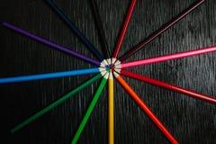 Beaucoup de crayons colorés sur un fond noir Crayons neufs Photos stock