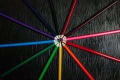 Beaucoup de crayons colorés sur un fond noir Crayons neufs Photo stock
