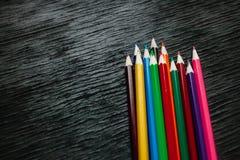 Beaucoup de crayons colorés sur un fond noir Crayons neufs Images libres de droits