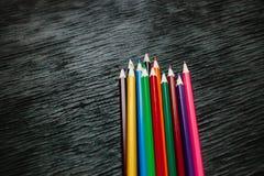 Beaucoup de crayons colorés sur un fond noir Crayons neufs Photo libre de droits
