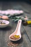 Beaucoup de différentes herbes médicinales dans des cuillères en bois sur un backg blanc Image stock