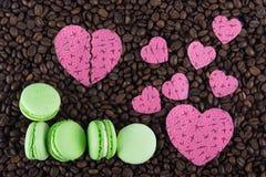 Beaucoup de différentes tailles des coeurs et des gâteaux aux pommes sur des grains de café Image libre de droits