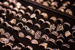Beaucoup de différents anneaux argentés sur le velours noir Photos stock
