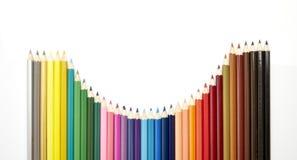Beaucoup de différents crayons colorés sur le blanc Photos stock