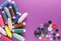 Beaucoup de différents fils de couture colorés et un grand choix de boutons sur un fond pourpre Images stock