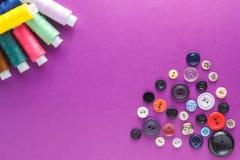 Beaucoup de différents fils de couture colorés et un grand choix de boutons sur un fond pourpre Photographie stock libre de droits