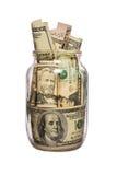 Beaucoup de dollars dans un pot en verre d'isolement sur le blanc Image stock