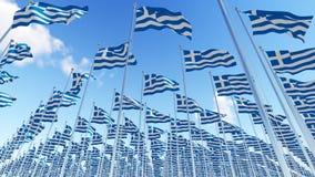 Beaucoup de drapeaux de la Grèce sur des mâts de drapeau contre le ciel bleu Photographie stock libre de droits