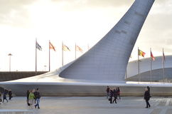 Beaucoup de drapeaux lumineux contre le ciel bleu et la torche olympique Photographie stock