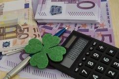 Beaucoup de 500 et 50 euro factures avec un trèfle à quatre feuilles, un stylo et a Image stock