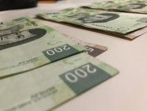 Beaucoup de factures de cinq cents et deux cents pesos mexicains distribués et de diffusion sur un bureau coloré beige photographie stock