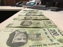 Beaucoup de factures de pesos mexicains ont distribué et diffusion sur un bureau coloré beige photo libre de droits