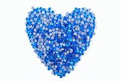 Beaucoup de fausses pierres bleues faites sous forme de coeur sur un fond blanc Vue supérieure Photos stock