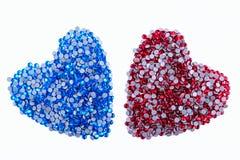 Beaucoup de fausses pierres rouges et bleues faites sous forme de coeur sur un fond blanc Vue supérieure Photographie stock