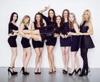 Beaucoup de femmes diverses dans la ligne, petites robes de fantaisie de port de noir, font la fête le maquillage, concept de pel Photos libres de droits