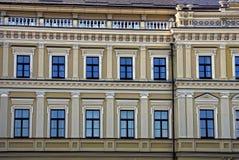 Beaucoup de fenêtres sur la façade gris-brune d'une grande maison Photo stock