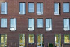 Beaucoup de fenêtres sur un mur brun d'immeuble de brique Photos libres de droits