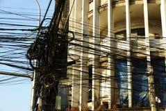 Beaucoup de fils électriques devant une façade d'art déco en Asie Photographie stock libre de droits
