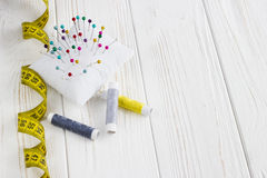Beaucoup de fils, mètre, boutons et goupilles de couleur sur en bois blanc Photos stock