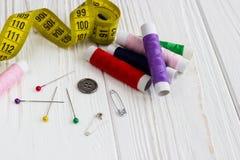 Beaucoup de fils, mètre, boutons et goupilles de couleur sur en bois blanc Photographie stock