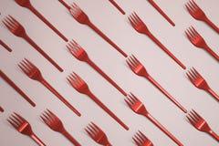 Beaucoup de fourchettes plasic vertes sur le fond rose, vue supérieure Modifié la tonalité en rouge photographie stock